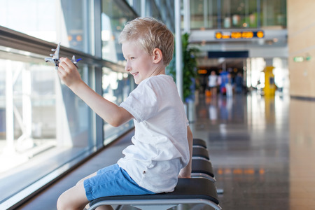 transportation travel: positive boy playing with toy plane at the airport waiting for departure and vacation Stock Photo