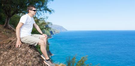 na: young man resting after hiking the kalalau trail at kauai island, hawaii