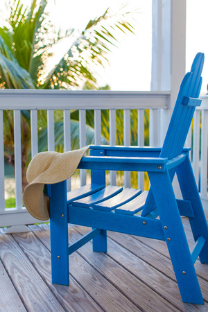 adirondack: blue empty adirondack chair with sunhat on it at the balcony or porch