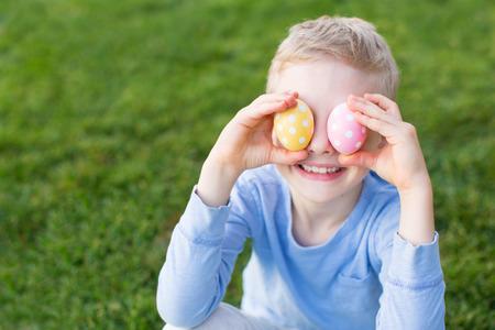 huevo blanco: Niño pequeño que sonríe ser juguetón en la primavera cubriendo sus ojos con coloridos huevos de Pascua después de la caza del huevo en el parque Foto de archivo