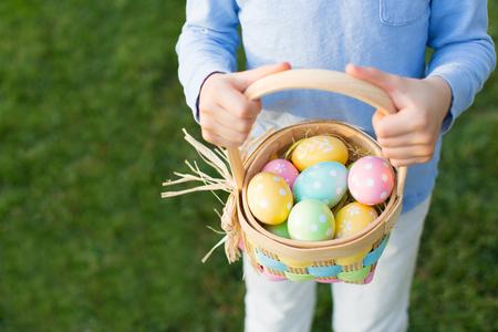 huevo blanco: Pascua y el concepto de la primavera, muchacho cesta celebraci�n llena de coloridos huevos de pie sobre la hierba