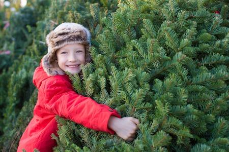 happy child holding christmas tree at christmas market at cold winter Reklamní fotografie