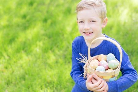 huevos de pascua: muchacho alegre celebración de la cesta llena de coloridos huevos de Pascua de pie sobre la hierba en el parque después de la caza del huevo Foto de archivo
