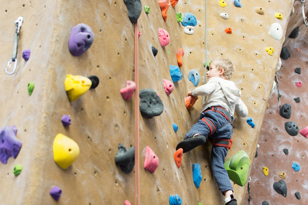 little active boy rock climbing at indoor gym 스톡 콘텐츠