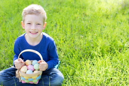 animal egg: cheerful boy holding basket full of colorful easter eggs sitting on the grass in the park after egg hunt Stock Photo