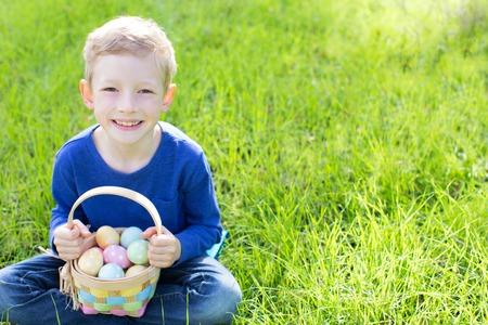 huevos de pascua: muchacho alegre celebración de la cesta llena de coloridos huevos de Pascua que se sientan en la hierba en el parque después de la caza del huevo