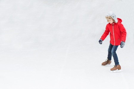 snow ice: positive happy boy enjoying winter vacation at outdoor ice skating rink learning ice skating