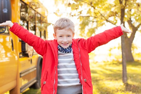 yellow schoolbus: excited schoolboy standing by the school bus ready for new school year