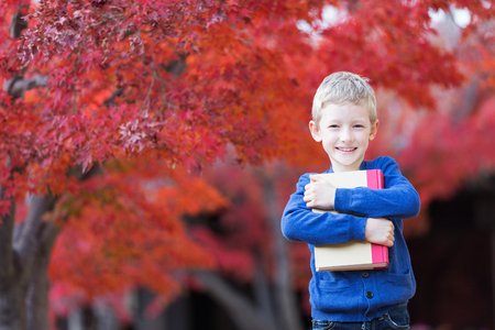 cool kids: beautiful little schoolboy holding book ready for new school year in the autumn park Stock Photo