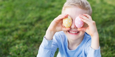 beautiful boy: panorama of little boy being silly and having fun at spring time covering his eyes with colorful eggs Stock Photo