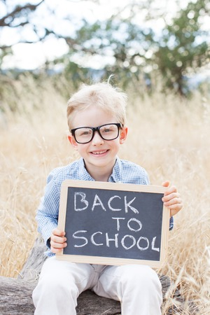 cool kids: cheerful schoolboy in glasses holding blackboard with back to school sign, back to school concept