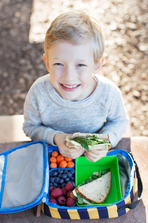 kids eating healthy: cheerful schoolboy eating healthy lunch outdoor