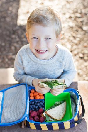 niños sanos: colegial alegre de comer el almuerzo al aire libre saludable Foto de archivo