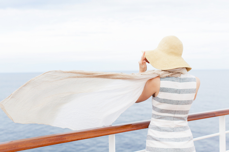 scarf: back view of young woman at cruise ship in sunhat and with waving at the wind scarf