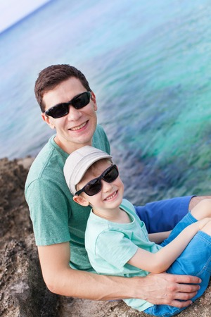 grand sons: family of two enjoying rocky beach at grand cayman, cayman islands, caribbean Stock Photo