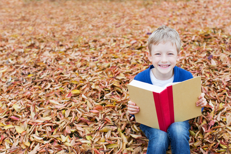 book concept: beautiful happy boy sitting in yellow leaves in autumn park with book, back to school concept Stock Photo