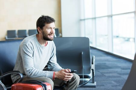 busy beard: handsome smiling man with a beard holding mobile phone and working at the airport, technology, travel and modern life concept