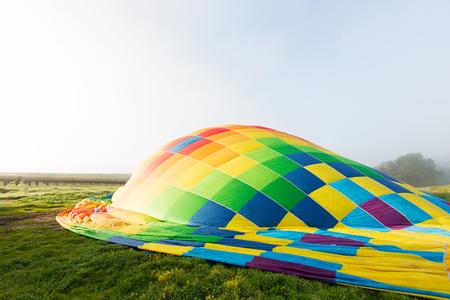 colorata mongolfiera sul terreno si prepara per il decollo Archivio Fotografico