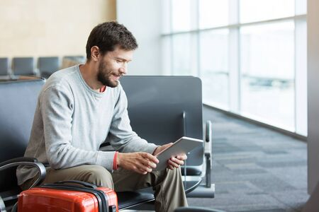 busy beard: handsome smiling man with a beard holding tablet and working at the airport, technology, travel and modern life concept Stock Photo
