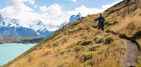 strenuous: panorama of young father and his son doing active and strenuous hike to mirador condor at torres del paine national park, patagonia, chile Stock Photo