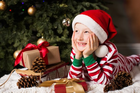 portrait of beautiful smiling boy lying by christmas tree at home enjoying winter time at home waiting for a miracle to happen Archivio Fotografico