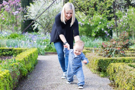 away: laughing cute toddler boy running away from young mother making first steps enjoying time together in the park Stock Photo