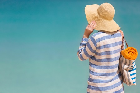 sun protection: back view at young woman at the beach in sunhat and cover enjoying perfect caribbean sea, sun protection concept Stock Photo