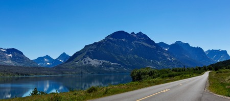 panorama view of road, lake and rocky mountains range in glacier national park, montana, usa