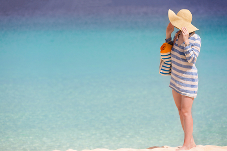 blue stripe: woman in sunhat and beach cover enjoying perfect caribbean beach, copyspace on side Stock Photo