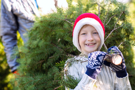beautiful smiling boy in santas hat, sweater and mittens holding with his father christmas tree, holiday concept Stock Photo