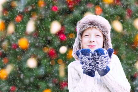 having fun in winter time: positive smiling child in trapper hat and warm winter clothes blowing snow, having fun and enjoying christmas time by the tree