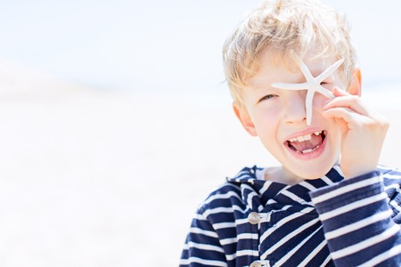 cheerful smlling positive boy winking and holding starfish in the hand being playful and enjoying nice weather at the beach, summer vacation concept, copyspace on the left