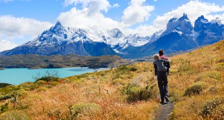 2 つの家族、父と息子、ハイキングとアクティブを楽しむ旅行トレス デル パイネ国立公園パタゴニア、チリ、cuernos 観でトレスデル ペインと pehoe 湖 写真素材