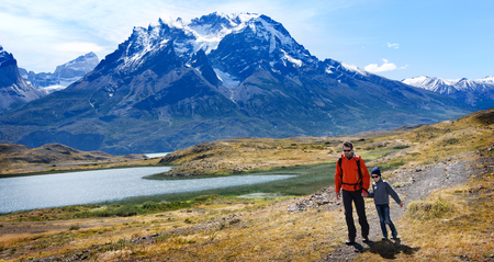 family of two, father and son, enjoying hiking and active travel in torres del paine national park in patagonia, chile, view of cuernos del paine