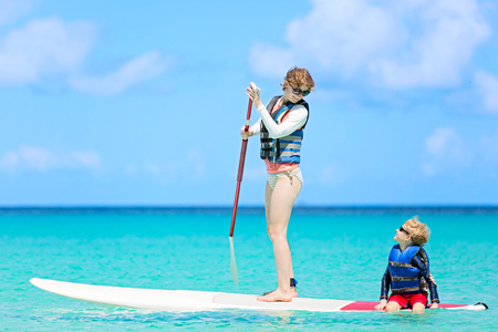 happy family of two, young mother and her little son, enjoying stand up paddleboarding in turquoise beautiful lagoon in caribbean, healthy summer vacation activity Stock Photo