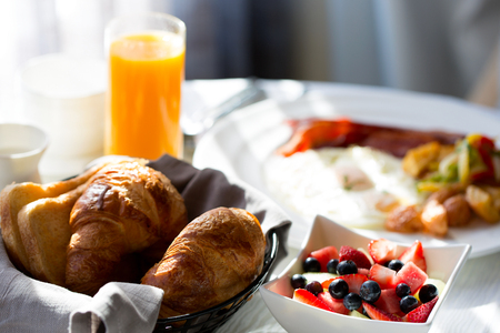 scrumptious: delicious healthy fruit bowl for breakfast with orange juice and pastries in the background, in-room dining at the hotel