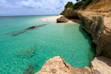 view of rocky rugged shore with white sand beach and turquoise lagoon at anguilla island Reklamní fotografie