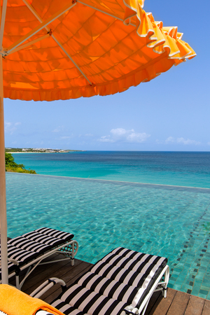 view at umbrella and two sunbeds by the infinity pool with gorgeous view of caribbean sea at anguilla island