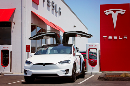 Seaside, CA - May 29, 2016: white tesla model x with falcon wing doors open charging at supercharger station