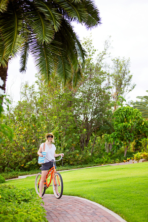 young woman riding bike during vacation at tropical island photo