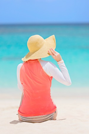 back view of young woman in rashguard and sunhat enjoying the perfect caribbean beach and protecting her skin from sun exposure during summer vacation, vacation concept photo
