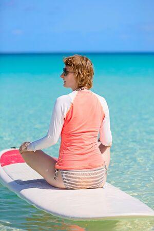young woman enjoying stand up paddling, active and healthy summer vacation activity photo