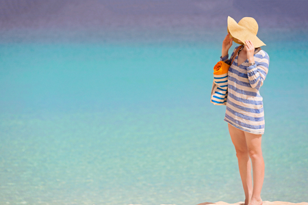 standing young woman enjoying the perfect caribbean beach during summer vacation, copyspace on the left photo