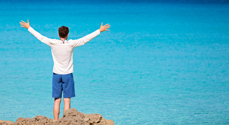 panorama of young man in rashguard and swimming shorts holding hands wide open and enjoying view of beautiful turquoise sea at perfect caribbean island, copyspace on right Stock Photo