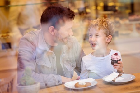 family of two, father and son, spending time together and enjoying desserts in cafe photo