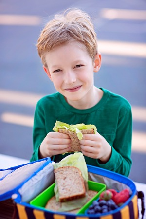 beautiful positive schoolboy enjoying healthy lunch during recess outdoor Stock Photo