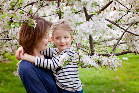 loving young mother and her little son enjoying time together and blooming spring trees, mother's day concept photo