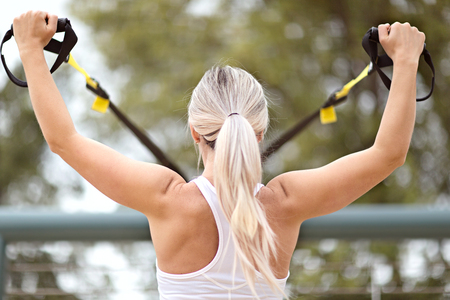 back view of young attractive woman doing upper body exercise training arms using trx suspension straps outdoor alone