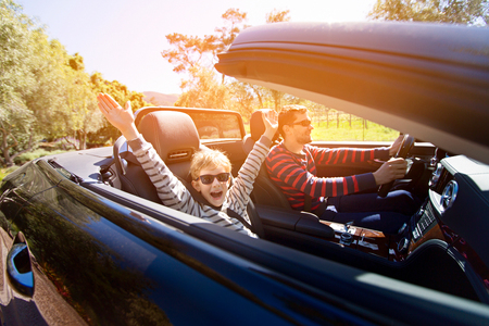 excited family of two, young father and his smiling son with hands high up in the air, enjoying road trip in convertible car, journey and vacation concept, sun flare