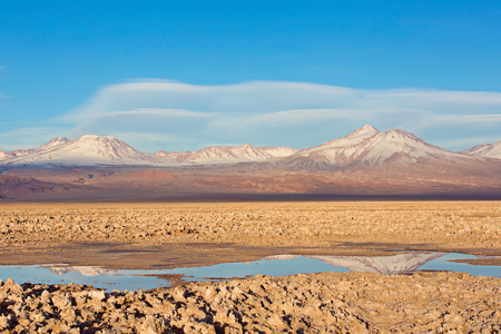 lenticular: beautiful landscape view of salty tebinquiche lagoon in atacama desert, chile with andes mountains in the background and lenticular clouds in the sky